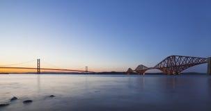 Framåt väg- och stångbroarna på nattskymningen Arkivfoto