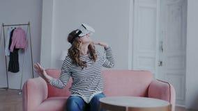Framtid är i dag Lycklig ung kvinna som testar exponeringsglas för en virtuell verklighet hemma Henne som flyttar sig och vänd lager videofilmer