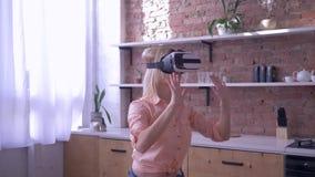 Framtid är nu, den unga kvinnan in i virtuell verklighetmaskering spelar den moderna leken hemma lager videofilmer