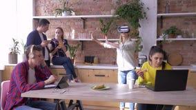 Framtid är nu, spelar den unga kvinnan med exponeringsglas av virtuell verklighetlekar, medan kollegor äter och kommunikationsstu arkivfilmer