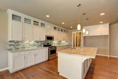 Framtidsutsikt på det lyxiga moderna köket i ett splitterny hus royaltyfri bild