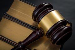 Framtvingande för laglig kod och rättssalförfarandebegrepp med en auktionsklubba på en bunt av lagböcker med den guld- kanten med royaltyfria foton