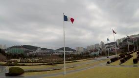 Francés, bandera que agita en el aire del cementerio conmemorativo de la O.N.U en Busán, Corea del Sur, Asia almacen de metraje de vídeo