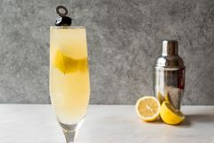 Francés 75 Champagne Cocktail con la cáscara de limón y la aceituna negra Imagenes de archivo