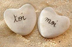 Francés usted y yo corazones de guijarros en la arena Imagen de archivo libre de regalías