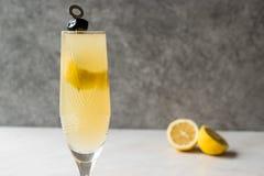 Francês 75 Champagne Cocktail com casca de limão e azeitona preta Fotografia de Stock Royalty Free