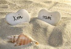 Francês você e mim corações dos seixos na areia imagem de stock royalty free