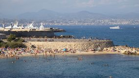 France, Antibes - August 28: Warm sea beach busy day in Antibes Stock Images