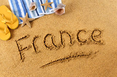 France beach summer sand word writing. The word France written on a sandy beach, with scuba mask, starfish and flip flops Stock Images