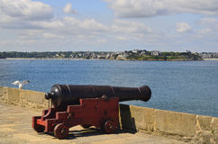 France, Brittany. France, medieval cannon on the St. Malo town wall with view to Dinard Village Royalty Free Stock Photography