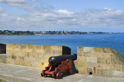 France, Brittany. Old cannon on the town wall of St. Malo with view to Dinard village Royalty Free Stock Image
