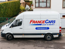 France Cars white renting van in French city. PARIS, FRANCE - DEC 02, 2015: France Cars van in front of luxury house - delivering goods. France Cars is the Stock Photos