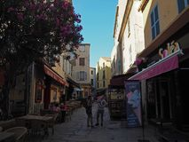 France, Corse, Calvi, June 6, 2017: street in old town with restaurant shops and young family. France, Corse, Calvi, June 6, 2017: street in old town with Stock Photography