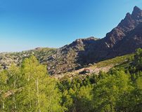 Corse View on refuge Ortu di Piobbu first part of GR 20 famous trek with green birch tree sharp mountain peak and blue sky Royalty Free Stock Image