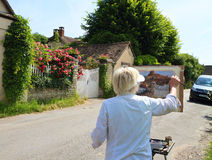 France/Giverny: Painting in Rue Claude Monet. This artist paints an idyllic scene in Claude Monet Street in Giverny. Claude Monet´s house, his beautiful flower Royalty Free Stock Images