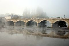 Fog over Amboise bridge. Fog over bridge with reflection in Amboise city in Loire valley in France Royalty Free Stock Image