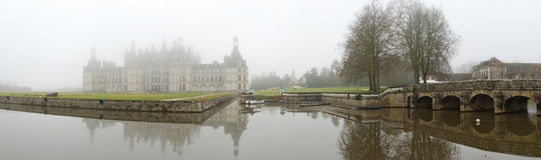 France. Loire Valley. Chambord castle. Panorama. France. Loire Valley. View on Chambord castle across the pond in winter fog. Panorama Stock Photos