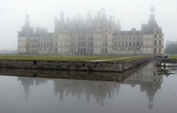 France. Loire Valley. View on Chambord castle. Across the pond in winter fog Royalty Free Stock Photos