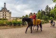 france Man och kvinna i forntida kläder på hästrygg mot bakgrunden av den kungliga slotten av Chambord Royaltyfria Foton