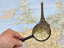 France map, miniature souvenir Eiffel tower, Paris. Miniature souvenir Eiffel tower over Paris on the map of France and Europe, through a magnifying lens Royalty Free Stock Photos