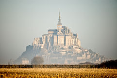 France Mont Saint Michel. The monastery of Saint Michael high on a rock in the ocean in the morning sun and the mist Royalty Free Stock Images