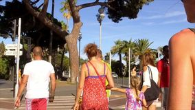 FRANCE NICE- 28 JULY: Young woman goes on a pedestrian crossing. View from the back stock video