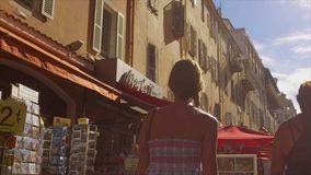 FRANCE NICE- 28 JULY: Young woman walking down the street in old Nice. View from the back stock video footage