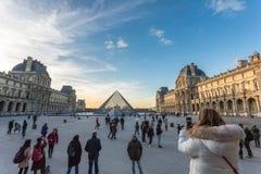 france paris Februari 2018: Louvremuseumsikt på solnedgången, med royaltyfria foton