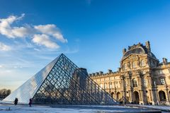 france paris Februari 2018: Louvremuseumsikt på solnedgången, med royaltyfria bilder