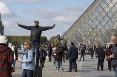 france paris folk som framme poserar av ingången av Louvre under kristallpyramiden royaltyfria bilder