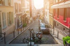 france paris Gator av Montmartre i solig höstafton i bakbelyst solnedgångsolstråle med tappningkameralense ser Arkivfoto