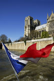 France, Paris, Notre Dame with French flag. Royalty Free Stock Photo