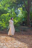 Elysian fields, young woman in a beautiful dress. France, Paris - 24 September 2017: Elysian fields. A young woman in a beautiful dress (pink gown) walking in stock image