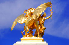 France, paris: Statues of Alexander III bridge. Blue sky and a gold wing horse with his amazone stock photo