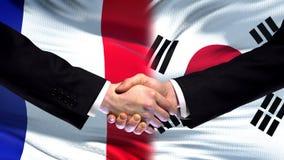 France and South Korea handshake, international friendship, flag background. Stock photo stock photos