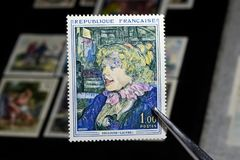 France Toulouse Lautrec. Tweezers hold a colorful postage stamp printed by France, Shows Toulouse Lautrec, circa 1965 Stock Photos