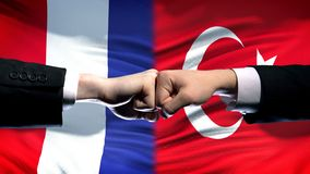 France vs Turkey conflict, international relations, fists on flag background. Stock photo royalty free stock images