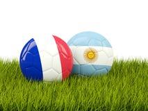 Frances contre l'Argentine Concept du football Les football avec des drapeaux sur le gre Photo stock