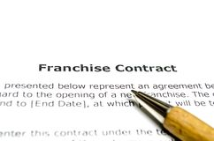 Franchise contract with wooden pen. Close up stock image