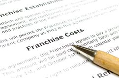 Franchise costs with wooden pen. Close up stock images