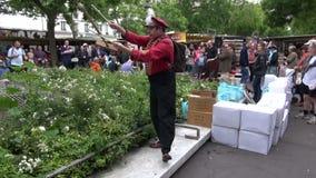FRANCIA, PARÍS: demostración de la calle del ejecutante del juglar con la escoba en el mercado de domingo almacen de metraje de vídeo