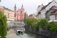 Franciscan kyrka p? Preserns gata och fartyg som korsar den Ljubljanica floden arkivfoton