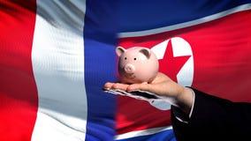 Francja inwestycja w korei północnej ręki mienia piggybank na chorągwianym tle obraz royalty free