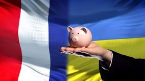 Francja inwestycja w Ukraina, ręki mienia piggybank na chorągwianym tle zdjęcie stock