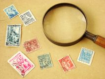 Francobolli del mondo e lente d'ingrandimento Fotografie Stock