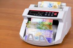 Francos suíços novos em uma máquina de contagem foto de stock