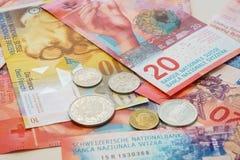 Francos suizos de billetes y monedas con las nuevas veinte cuentas del franco suizo Foto de archivo libre de regalías