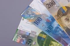 Francos suizos en fondo o textura de madera gris imagen de archivo libre de regalías