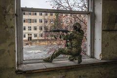 Francotirador de Airsoft en la ventana Contra la perspectiva de las ruinas de edificios imagen de archivo libre de regalías