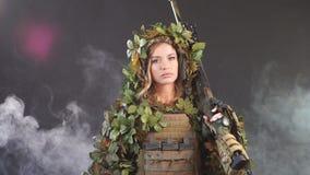 Francotirador del soldado de la mujer en disfraz con el rifle de francotirador y objetivos en oscuridad ahumada